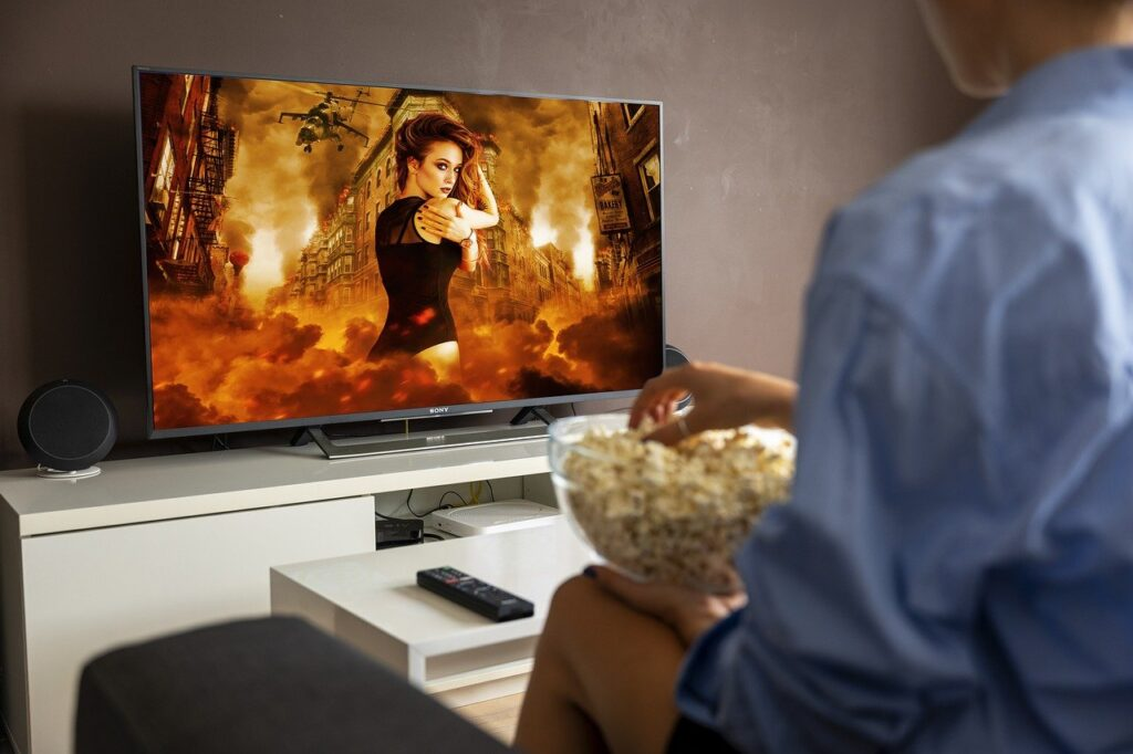 A person hold popcorn and sitting in front of the tv